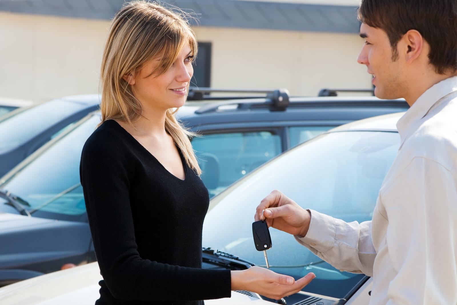 a car dealer gives a woman her car keys